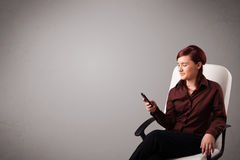 Young lady sitting and holding a phone with copy space Stock Photo