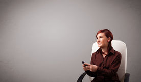 Young lady sitting and holding a phone with copy space Stock Photography
