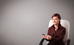 Young lady sitting and holding a phone with copy space Stock Photos
