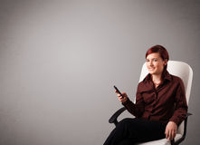 Young lady sitting and holding a phone with copy space Stock Images