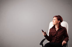 Young lady sitting and holding a phone with copy space Royalty Free Stock Image
