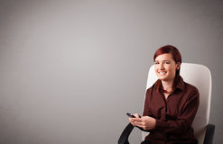 Young lady sitting and holding a phone with copy space Royalty Free Stock Photos