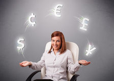 Young lady sitting and juggling with currency icons Royalty Free Stock Photos