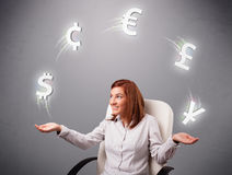 Young lady sitting and juggling with currency icons Royalty Free Stock Photo