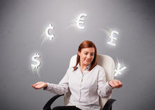 Young lady sitting and juggling with currency icons Royalty Free Stock Images