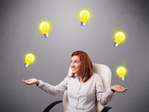 Young lady sitting and juggling with light bulbs Royalty Free Stock Photography