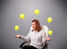 Young lady sitting and juggling with light bulbs Stock Photo