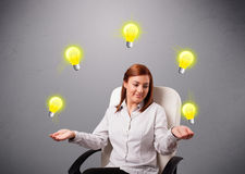 Young lady sitting and juggling with light bulbs Stock Image