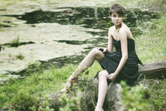 Young lady sitting near pond Stock Photo