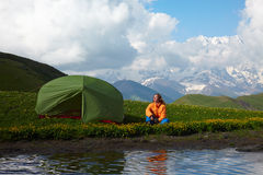 Young lady sitting near a tent in front of snowy mountain peaks Stock Images