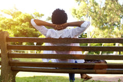 Young lady sitting relaxed on a park bench Royalty Free Stock Photo