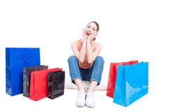 Young lady sitting with shopping bags around and feeling cheerful royalty free stock images