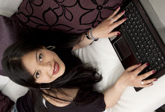 Young lady sitting on sofa with laptop Royalty Free Stock Photo