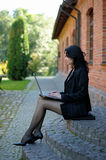 Young lady sitting on stone steps with a notebook. Beautiful young lady sitting on stone steps with a notebook Royalty Free Stock Photo