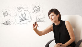 Young lady sketching financial chart icons and symbols. On white background Stock Photo
