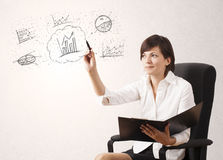 Young lady sketching financial chart icons and symbols. On white background Royalty Free Stock Images