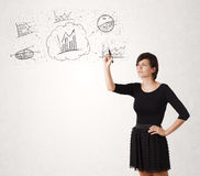 Young lady sketching financial chart icons and symbols. On white background Stock Photos