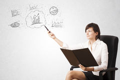 Young lady sketching financial chart icons and symbols Royalty Free Stock Photography