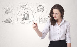Young lady sketching financial chart icons and symbols Royalty Free Stock Image
