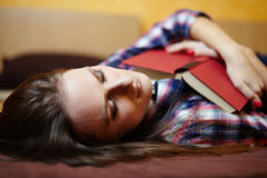 Young lady sleeping with a book on the bed Royalty Free Stock Photography
