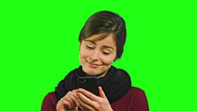 A Young Lady Chatting on the Phone. A young lady smiling and chatting on the phone against a green background. Close-up shot Royalty Free Stock Image