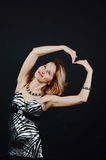 Young lady smiling. With her hands in a shape of heart Stock Photography