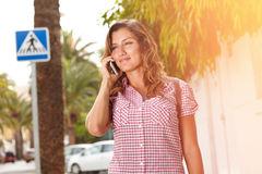 Young lady smiling while speaking on mobile phone Royalty Free Stock Photo