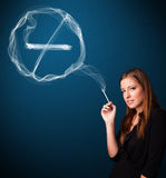 Young lady smoking unhealthy cigarette with no smoking sign Royalty Free Stock Photography