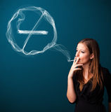 Young lady smoking unhealthy cigarette with no smoking sign Stock Images