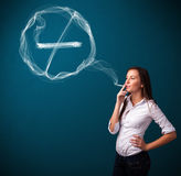 Young lady smoking unhealthy cigarette with no smoking sign Stock Photos