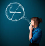 Young lady smoking unhealthy cigarette with no smoking sign Royalty Free Stock Photo