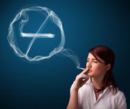 Young lady smoking unhealthy cigarette with no smoking sign Stock Image