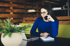 Young lady speak on phone at work. In modern office Stock Image