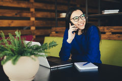 Young lady speak on phone at work. In modern office Stock Images