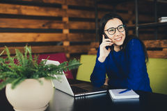 Young lady speak on phone at work. In modern office Royalty Free Stock Images