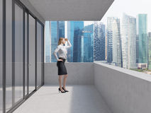 Young lady is standing on the balcony of the skyscraper and looking at the new business perspectives. Singapore panoramic. Young business lady is standing on the Royalty Free Stock Image
