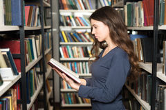 Young lady standing between book shelves in the library reading Stock Photos