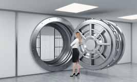 Young lady standing in front of a big unlocked round metal safe Royalty Free Stock Photo