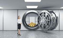 Young lady standing in front of a big unlocked round metal safe. In a bank depository with a pyramid of gold bars and lock-boxes inside,  a concept of security Stock Photography
