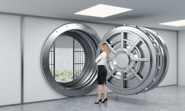 Young lady standing in front of a big unlocked round metal safe Royalty Free Stock Photography