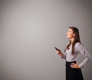 Young lady standing and holding a phone Royalty Free Stock Photography