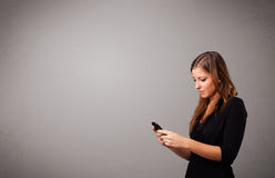 Young lady standing and holding a phone with copy space Stock Photo