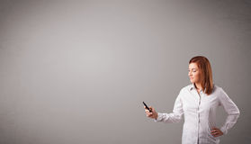 Young lady standing and holding a phone with copy space Royalty Free Stock Photography