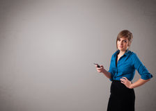 Young lady standing and holding a phone with copy space Stock Photography