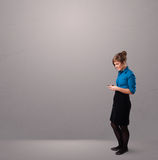 Young lady standing and holding a phone with copy space Royalty Free Stock Image