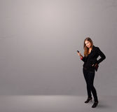 Young lady standing and holding a phone with copy space Stock Images