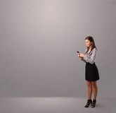 Young lady standing and holding a phone with copy space Royalty Free Stock Photo