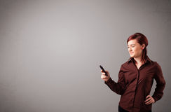Young lady standing and holding a phone with copy space Stock Image