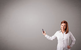 Young lady standing and holding a phone with copy space Royalty Free Stock Photos