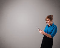 Young lady standing and holding a phone with copy space Stock Photos